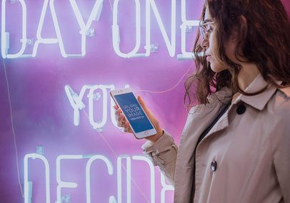 Mockup of a Woman Holding a Rose Gold iPhone 7 Plus by a Neon Sign a21293