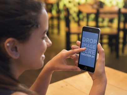 Woman Using Black iPhone 6 At a Restaurant