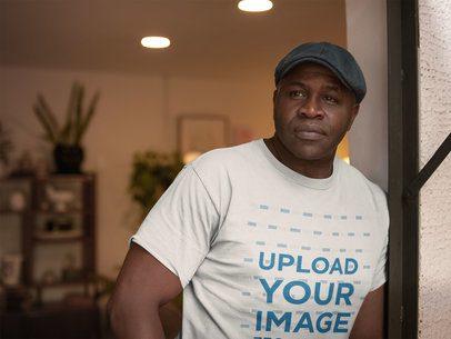Mockup of a Senior Black Man Wearing a T-Shirt and a Beret at Home a21432