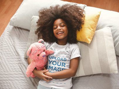 T-Shirt Mockup of a Smiling Black Girl with Curly Hair on Bed a21319