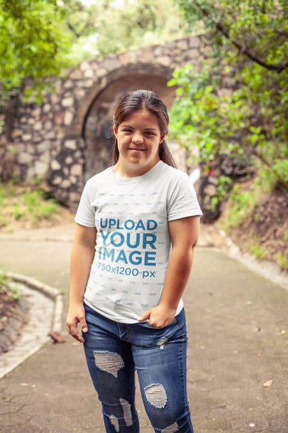 T-Shirt Mockup of a Smiling Girl Standing Near a Bridge at a Park a21378