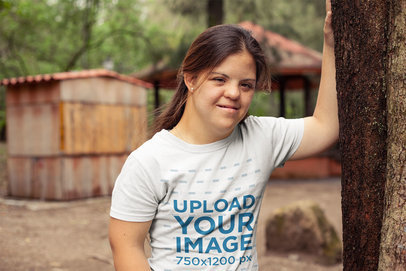 Round Neck Tee Mockup Featuring a Girl with Down syndrome Leaning Against a Tree with One Arm a21383