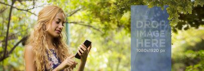 Beautiful Mockup of Blonde Girl Using Her Smartphone Below a Tree