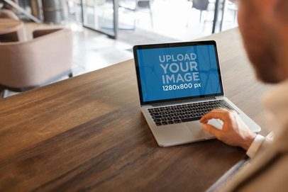 Mockup of a Businessman Using a MacBook on a Wooden Table a20993