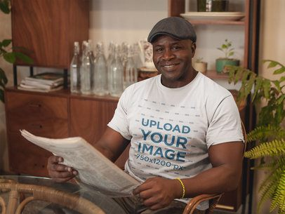 Mockup of a Smiling Man Wearing a Round Neck T-Shirt Reading the Newspaper a21430