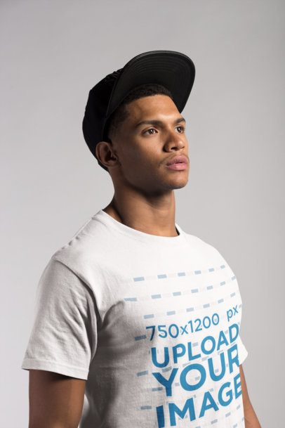 Angled Shot of a T-Shirt Mockup Featuring a Young Man with a Hat 21071