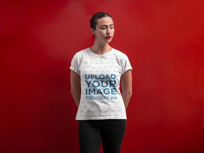 Mockup of a Woman Wearing a T-Shirt Against a Red Wall a21317