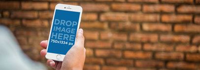 Mockup Template of an iPhone 6 Against a Brick Wall