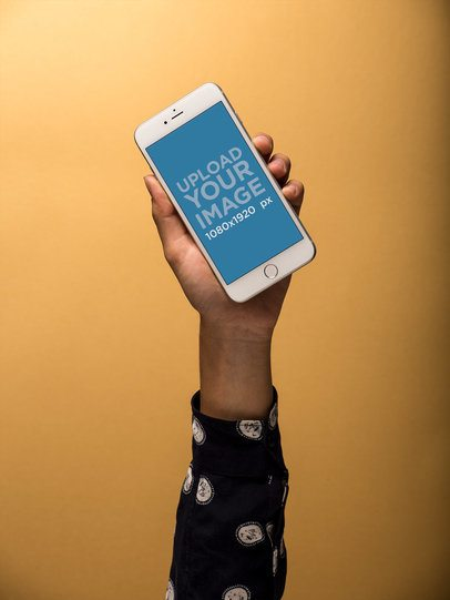Mockup of an Arm Holding an iPhone Against a Yellow Wall 21776