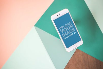 iPhone Mockup Floating Over a Wooden Table with Green and Pink Shapes 21614