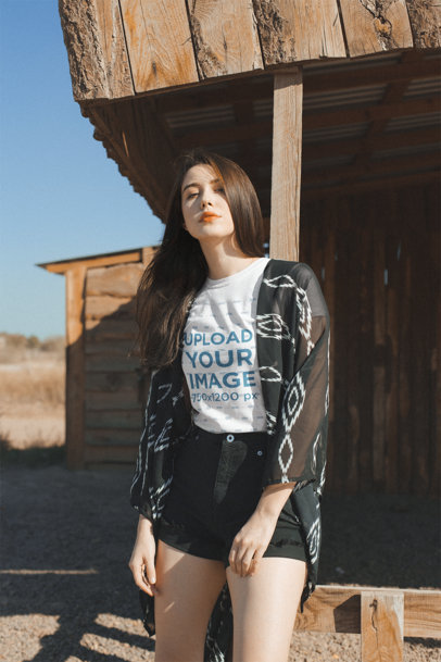 Mockup of a Cool Young Woman Wearing a T-Shirt Leaning On a Wood Cabin in the Desert 18874