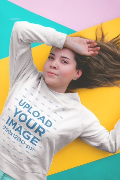 Sweatshirt Mockup Featuring a Girl Lying on a Colorful Geometric Background 18422