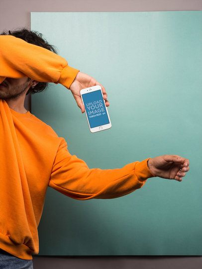 Silver iPhone 8 Plus Mockup Held by a Man in an Orange Sweatshirt Covering His Face 21772