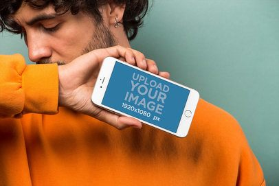 Mockup of an iPhone 8 Plus Held by a Man in Front of a Cyan Background 21773