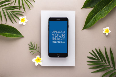 Mockup of a Gold iPhone 8 Plus Surrounded by Leaves and Plumeria Flowers 21825