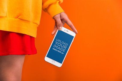 Mockup of the Hand of a Woman Showing a Silver iPhone 8 Against a Vivid Orange Background  21970