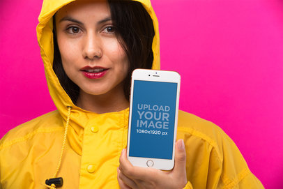 Mockup of an iPhone 8 Plus Held by a Woman Wearing a Bright Yellow Raincoat 21972