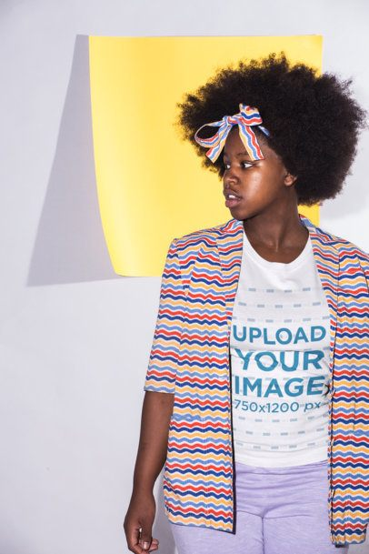 T-Shirt Mockup of a Young Woman with Afro Hair Wearing a Colorful Outfit Against a Square Yellow Paper 21715