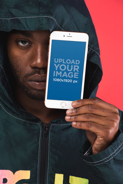 Mockup Featuring a Serious-Looking Man Holding a Gold iPhone 8 Plus in Front of His Face 22126