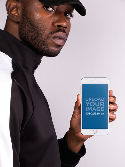 Mockup of a Man in a Street Style Outfit Holding an iPhone 8 Plus 22133