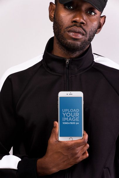 iPhone 8 Plus Mockup Held by a Serious Man Wearing Black 22131