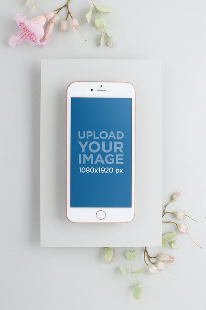 Mockup of an iPhone on a Matte White Cardboard Environment with Flowers 22136