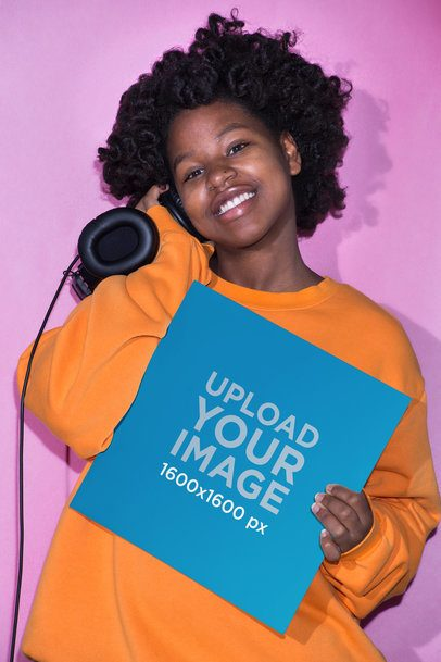 Mockup Featuring a Smiling Girl with Headphones Showing a Vinyl Record Cover Against a Pink Background 22114