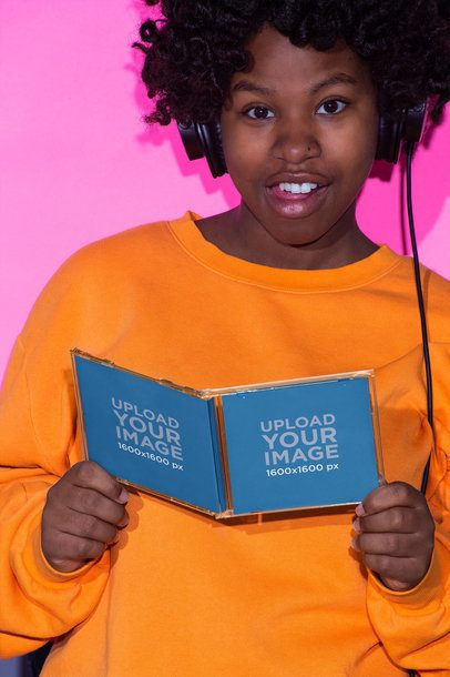 Mockup Featuring a Woman with an Afro Style and Orange Sweatshirt Holding a CD Cover 22122