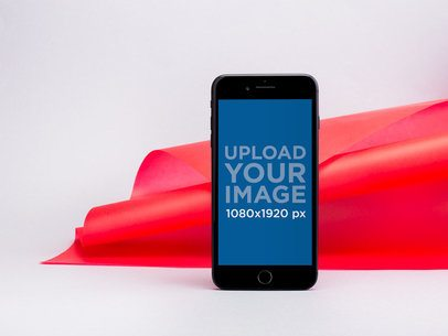 iPhone 8 Mockup Standing Against a Bent Red Paper 22194