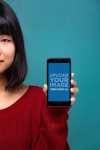 Mockup Showing a Space Gray iPhone 8 Plus Being Held Against a Dark Cyan Background 22165