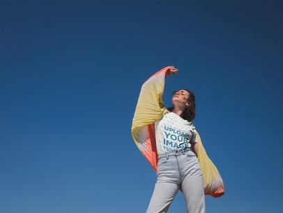 T-Shirt Mockup of a Woman Standing In Front of a Clear Blue Sky 20019