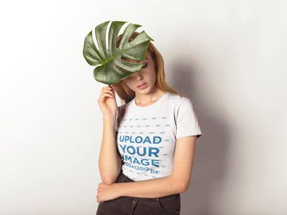 T-Shirt Mockup of a Woman Holding a Large Leaf to Her Head 18385