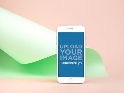 iPhone 8 Plus Mockup Standing Against a Light Green Folded Cardboard 22191