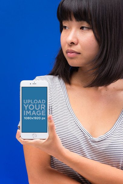 Mockup of a Serious Woman with an iPhone 8 Against a Bright Blue Background 22175