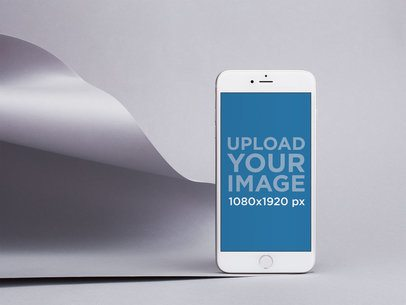 Silver iPhone 8 Mockup Standing by a Silver Pasteboard in a Gray Room 22192