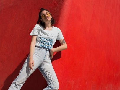T-Shirt Mockup of a Girl with Jeans and Vintage Glasses Against a Red Wall 20020
