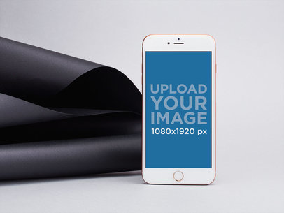 iPhone 8 Plus Mockup Leaning Over Black Spiraled Cardboard 22193