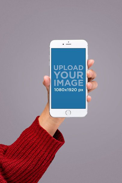 Silver iPhone 8 Mockup Held by Someone Wearing a Red Knit Sweater 22182
