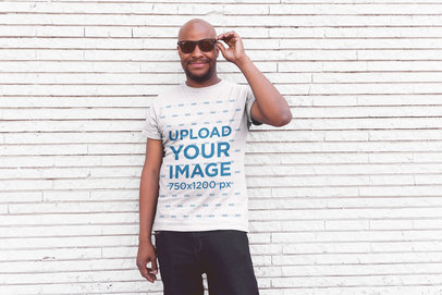 T-Shirt Mockup of a Smiling Middle-Aged Man Posing in Front of a White Wall 20774