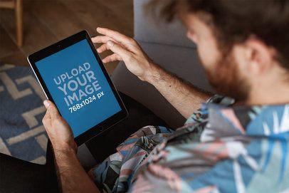 Overshoulder iPad Mockup of a Man Wearing a Shirt on his Sofa 22603
