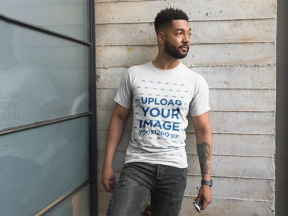 Front View T-Shirt Mockup Featuring a Man with a Beard Against a Concrete Wall and a Window 21352