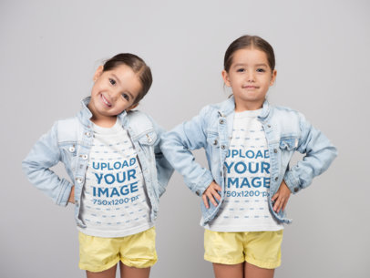 Crew Neck T-Shirt Mockup Featuring Twin Sisters Posing while Wearing Denim Jackets and Yellow Shorts 22520