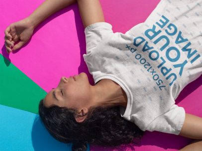 Tshirt Mockup of a Girl Resting Over Colorful Pasteboards 18427