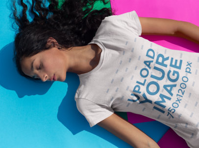 Tee Mockup of a Woman Lying in the Sun Over Colorful Cardboard 18431