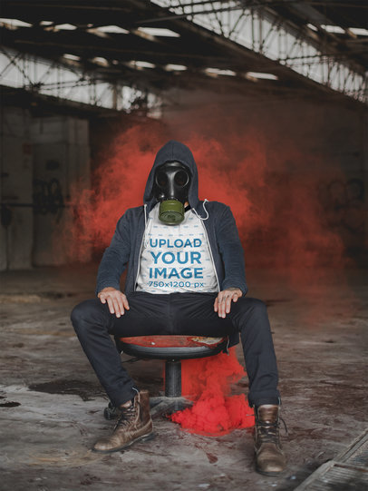 T-Shirt Mockup of a Man with a Gas Mask Sitting Near Red Smoke 22946