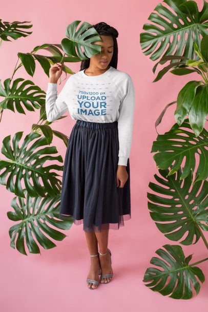 Mockup of a Girl Wearing a Crewneck Sweater in a Pink Studio with Plants 18398