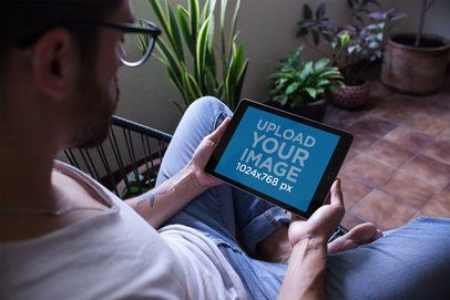 Mockup of a Man with Tattoos Holding an iPad in Landscape Position Sitting on an Acapulco Chair 22816