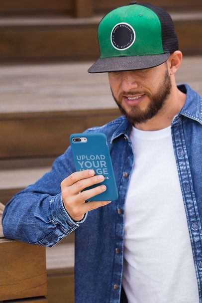 Phone Case Mockup Held by a Man with a Black and Green Hat 22875