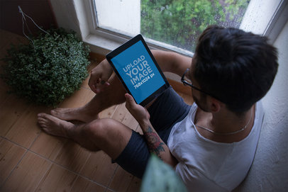 Mockup of an iPad Held by a Man Sitting Next to a Window on a Rainy Day 22827