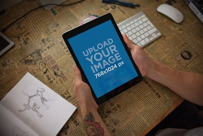 Mockup of an iPad Held by a Man Over his Desk 22833